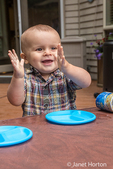 Fourteen month old happy toddler boy showing how he can clap his hands, as he plays outside with plastic plates, using a spa cover for a table