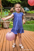 Three year old girl playing with a paper lantern on a cedar wood deck