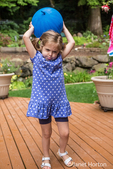 Three year old girl playing with a balloon, looking like she is struggling, in Issaquah, Washington, USA