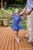 Three year old girl trying to catch a balloon, with her father behind her