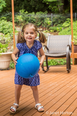 Three year old girl playing with a balloon