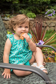 Eighteen month old girl sitting in a patio chair outside eating a granola bar