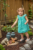 Eighteen month old girs walking outside in a garden where there are urns of ashes from pet dogs