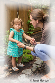 Thirty-four year old mother holding eighteen month old daughter's hands as she stands in a backyard garden