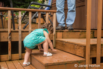 Eighteen month old toddler girl struggling to climb the stairs on the wooden deck, as her grandfather watches her progress