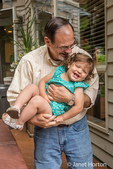 Grandfather playfully holding his eightteen month old granddaughter on the deck of his backyard