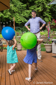 Father playfully acting brave when his three and one year old daughters are going to throw balls at him
