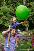 Thirty-four year old father holding his three year old daughter as she catches a balloon tossed to her