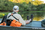 Male tourist in a tour boat waiting for a jaguar to move on a river safari in the Pantanal area of Brazil.