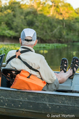 Male tourist in a tour boat waiting for a jaguar to move on a river safari