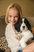 Portrait of a seven year old girl cuddling with her two month old Springer Spaniel puppy, Tre