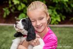 Seven year old girl holding and hugging her two month old Springer Spaniel puppy, Tre