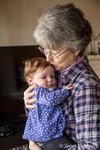 Three month old baby girl being kissed by her grandmother
