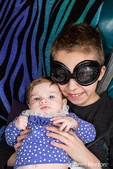 Fourteen year old boy wearing goggles holding his three month old sister