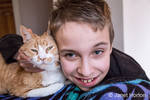 14 year old boy hugging Kia, his domestic short-hair cat