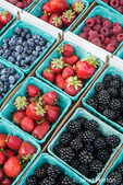 Pints of freshly harvested strawberries, blueberries and blackberries for sale at a Farmer's Market