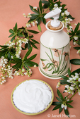 Lotion in an attractive pottery container, surrounded by white Lily of the Valley bush blossoms in a studio setting