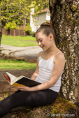 Eleven year old girl reading a book in the shade of a tree
