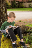 Nine year old boy reading a book in the shade of a tree in Issaquah, Washington, USA