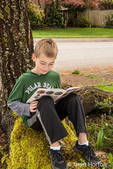 Nine year old boy reading a book in the shade of a tree