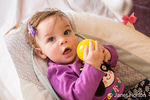 Six month old baby girl playing with a yellow plastic ball in her swing