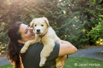 "Backlit woman affectionately holding her Golden Retriever puppy ""Ivy"""