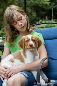 Ten year old girl sitting on a patio chair, holding her two month old Brittany Spaniel