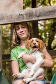 "Ten year old girl holding her two month old Brittany Spaniel ""Archie"" while sitting on a backyard slide in Issaquah, Washington, USA"