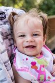Happy nine month old girl as she eats soft apple chunks outside
