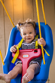 Happy nine month old girl outside in her swing.  She yells