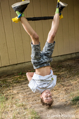 Fourteen year old boy demonstrating his prowess on the trapeze bar in his backyard