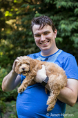 "Twenty something man holding his eight week old Goldendoodle puppy ""Bella"" in Issaquah, Washington, USA"