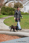 Woman walking her black Pug in an urban park