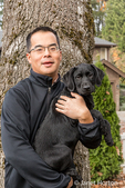 "Man holding ""Shadow"", his three month old black Labrador Retriever puppy, in Bellevue, Washington, USA"