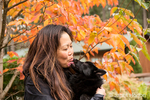"Woman holding her Schipperke puppy ""Cash"" while he gives her ""doggy kisses"" on an Autumn day in Maple Valley, Washington, USA"