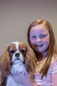 "Portrait of a seven year old girl holding her Cavalier King Charles Spaniel puppy ""Bode"" in Maple Valley, Washington, USA"