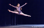 Twelve year old girl performing a straddle leap at a dance recital