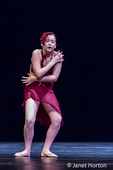 Twelve year old girl performing a solo lyrical dance onstage, conveying sadness and grief