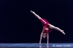 Twelve year old girl performing a solo lyrical dance onstage, doing a cartwheel to the floor