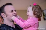 One year old girl having fun pinching her dad's cheeks