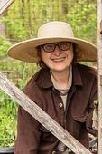 Portrait of a gardener planting seeds beside a wooden trellis in a spring garden