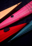 Four sea kayak bows, one of fiberglass, one of wood, one of roto-molded plastic and one of fabric and aluminum frame,