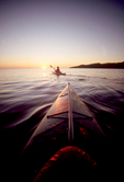 Baja, Mexico, Sea Kayaking, Female sea kayaker paddles beyond bow kayak toward sunrise, Sea of Cortez, Gulf of California, Baja Sur,