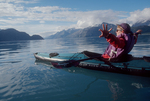 Alaska, Glacier Bay National Park, Woman kayaker celebrating, stretching in sunshine, Alaska's John Hopkins Inlet.