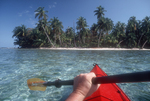 Belize, Lime Cay, Caribbean Sea, Central America, sea kayaker paddling off white sand beach,