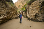 CALIFORNIA - Hiker walking between colorful sandstone cliffs and seastacks on Sculptured Beach in Point Reyes National Seashore.