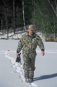 Man ice fishing (tip-up in background)
