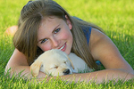 Teenager holding sleeping yellow Labrador retriever puppy