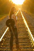 Teenager carrying her guitar as she pauses to look back
