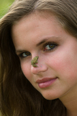 Juvenile wood frog on the nose of a young woman